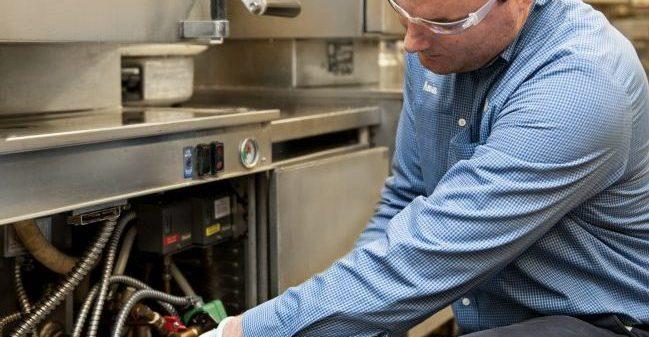 contractor repairing commercial food equipment