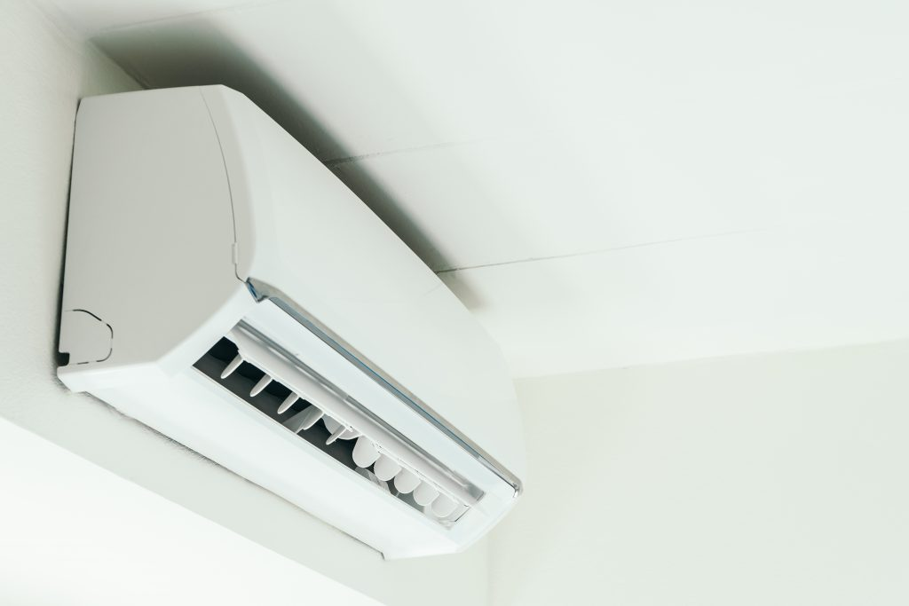 A wall-mounted mini-split system installed near the top of a wall.