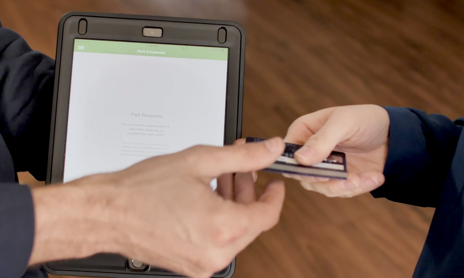 Scene from Kemco Services testimonial video showing customer paying with card on tablet with FieldEdge.
